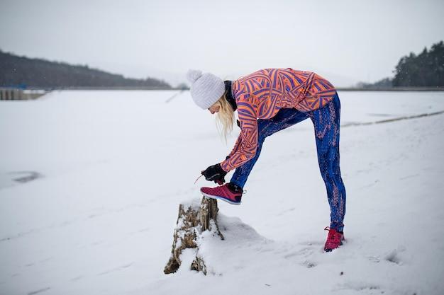 눈 덮인 겨울에 야외에서 활동적인 수석 여성, 신발끈을 묶습니다.