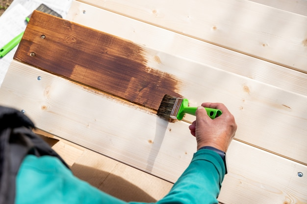 Active senior woman painting some pieces of wood, timber by brown paint colour with brush.worker painting a wooden wall