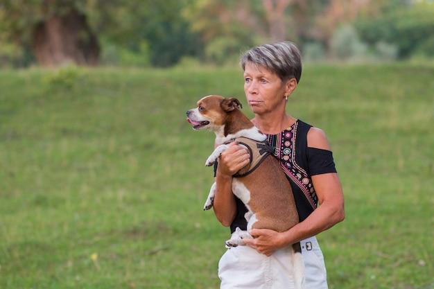 Активные пожилые люди моды женщина держит свою маленькую собаку