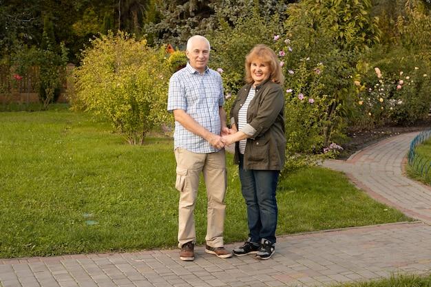 夏の森を散歩するアクティブな先輩、春夏の時期に年配のカップルがリラックス。