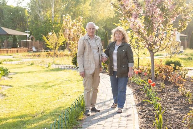 夏の公園で散歩にアクティブシニア、年配のカップルは春夏の時間でリラックスします。ヘルスケアライフスタイル高齢者退職愛カップル一緒にバレンタインデーのコンセプト