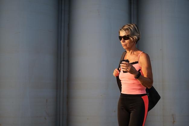 アクティブな高齢者の女性は、コーヒー、スポーツバッグ、スマートウォッチ、サングラスを使って、市内でフィットネストレーニングを行います。スポーティなフィットネス。日没。健康的な生活様式。高品質の写真