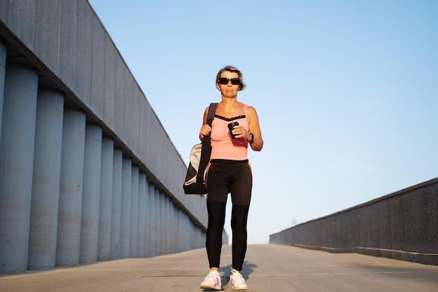 アクティブな高齢者の女性は、市内でフィットネストレーニングに行きます