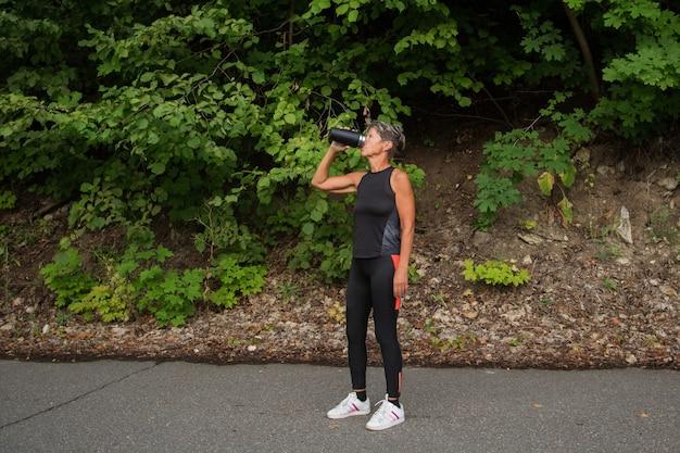 Активная женщина пожилых людей в фитнес-костюме, держащая термо