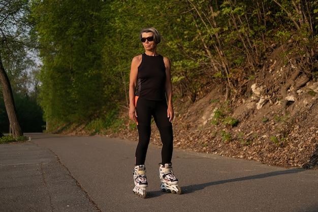 屋外の公園でアクティブな高齢者女性ローラーブレード