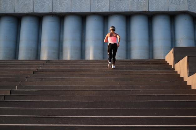 市内の階段で走っているアクティブな高齢者の女性