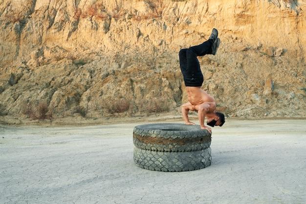 타이어에 균형을 맞추고 모래 구덩이에서 훈련하는 동안 다리를 들고 활동적인 shirtless 남자. 유행성 기간 동안 검은 보호 마스크를 쓰고 근육 질의 남자.