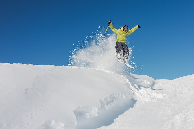 Active skier in yellow sportswear riding down the slope in georgia, gudauri