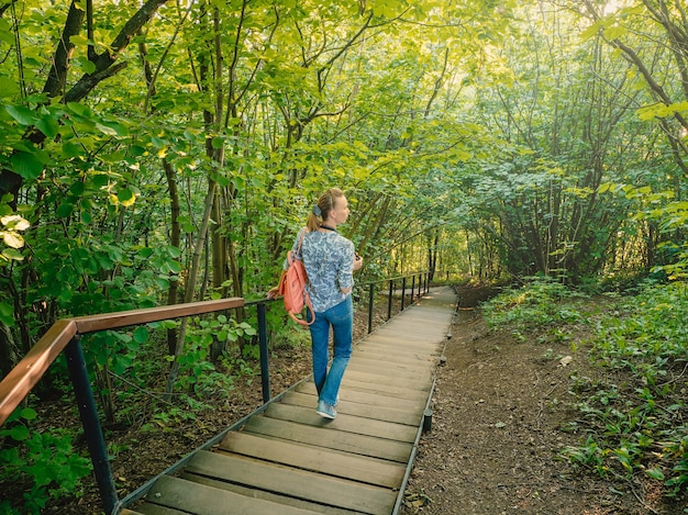 Active slender woman with a backpack a steep staircase in green forest. eco trail in the park.