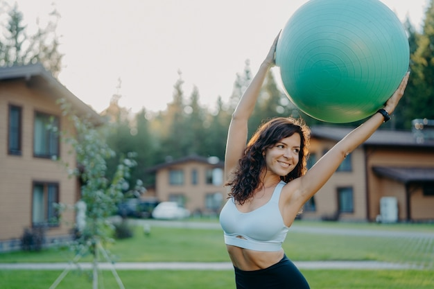 Active slim dark haired young woman with perfect body keeps big fitness ball over head, looks away with smile, dressed in active wear, poses outdoor near house, has yoga exercises in open air