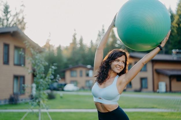 完璧なボディを持つアクティブなスリムな黒髪の若い女性は、大きなフィットネスボールを頭上に保ち、笑顔で目をそらし、アクティブな服を着て、家の近くで屋外でポーズをとり、屋外でヨガの練習をします