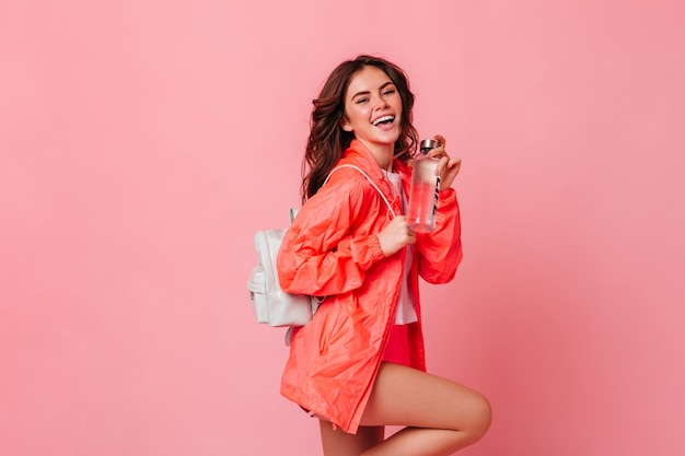 Active slim woman in sports jacket and with backpack laughs and holds bottle of water on pink wall