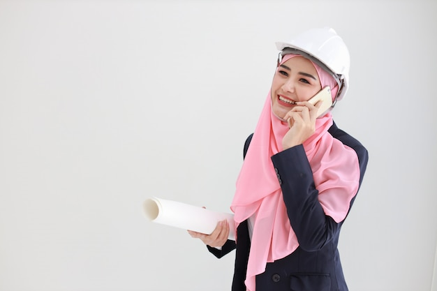 Active and smart muslim young asian woman in blue suit smiling confident holding blueprint and using mobile phone