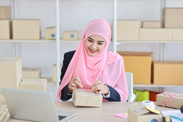 Active smiling asian muslim woman in blue suit sitting and working