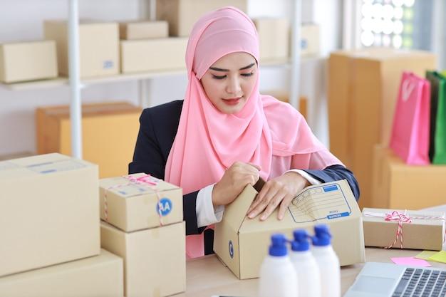 파란색 정장 앉아서 온라인 패키지 상자 배달 작업에 활성 웃는 아시아 이슬람 여자. 시작 중소 기업 중소기업 프리랜서 소녀는 행복 한 얼굴로 컴퓨터와 휴대 전화에서 작업.