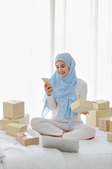 Active smiling asian muslim woman in sleepwear sitting on bed using mobile phone and computer. startup small business sme freelance woman working with online package box delivery, e-commerce concept.