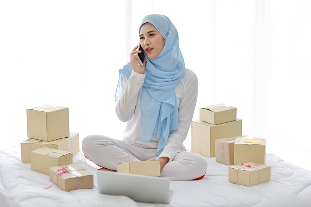Active smiling asian muslim woman in sleepwear sitting on bed using mobile phone and computer