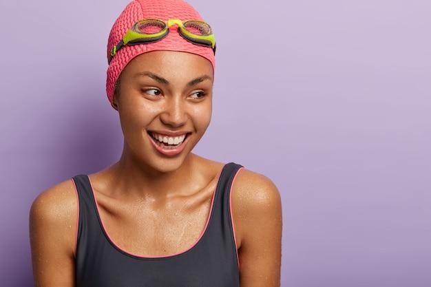 활동적인 웃는 검은 피부의 여성 수영 선수는 경쟁을 준비하고 다이빙 후 젖어 있으며 수영 의상, 모자 및 고글을 옆으로 치우고 스포티 한 몸매를 가지고 있습니다. 레크리에이션 및 취미