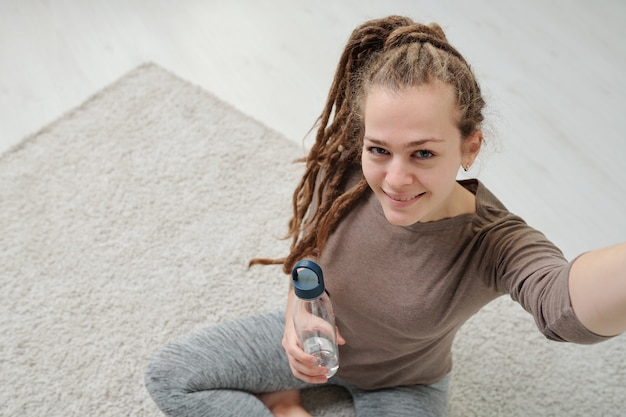 Active smiling girl with bottle of water looking at camera while making selfie after yoga practice on the floor