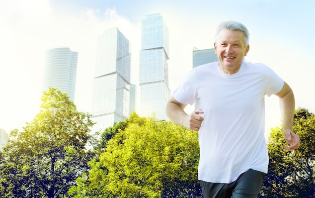 Active smiling mature man jogging in the park on business city and sky background