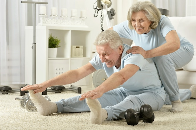 집에서 운동하는 활성 미소 수석 부부