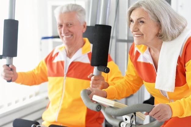 체육관에서 운동하는 활성 웃는 수석 부부