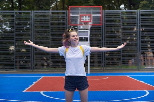 Активная улыбающаяся девочка-подросток, модная с фиолетовыми волосами, на уличной баскетбольной площадке с поднятыми руками. эмоция счастья, праздника, веселья