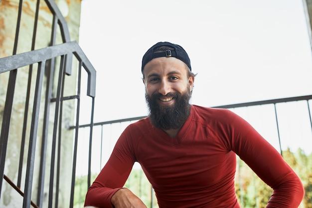 Active smilling bearded sportsman having rest and sitting on stairs in bright day.