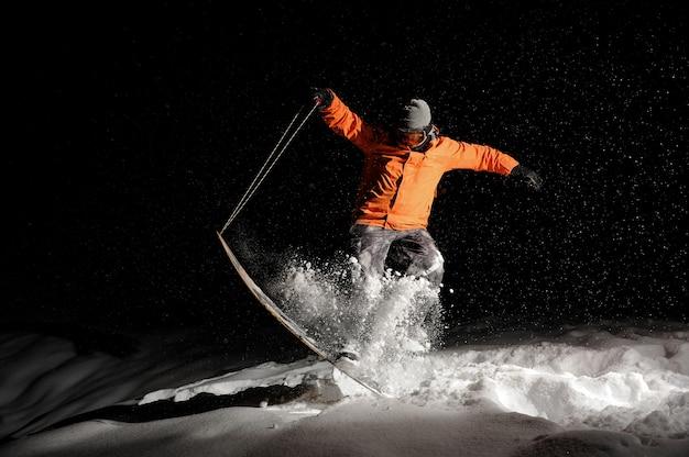 Активный сноубордист в оранжевой спортивной одежде и маска прыгает на снежной горке ночью