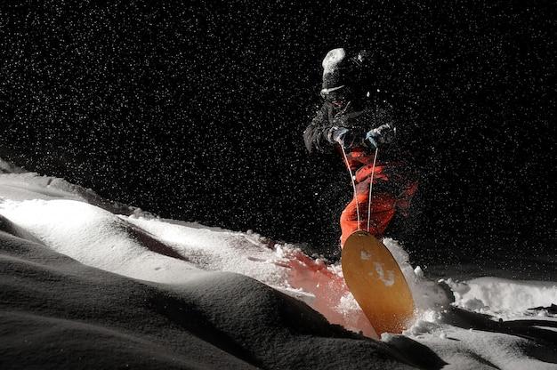 Активный сноубордист едет по снежной горке ночью