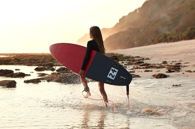 アクティブなスポーツとライフスタイルのコンセプト。ボードサーファーは動いていて、赤いサーフボードを運び、水にぶつかり、サーフィンのための暇な時間を楽しんでいます
