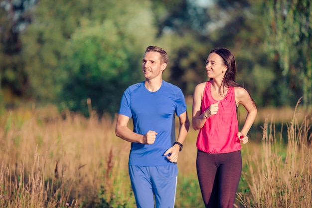 Active sportive couple running in park. health and fitness.