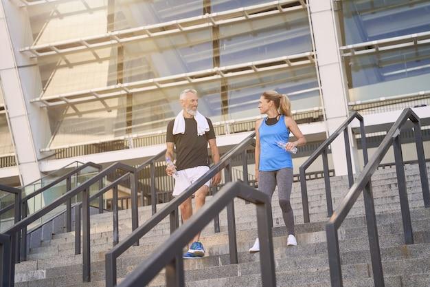運動後の階段を歩いてスポーツウェアのアクティブなスポーツ成熟したカップルの男性と女性