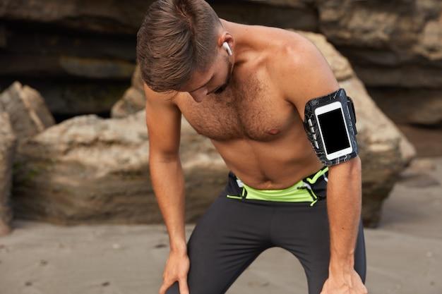 활동적인 스포츠맨이 야외에서 장거리 달리기를 취재 한 후 숨을 쉬다