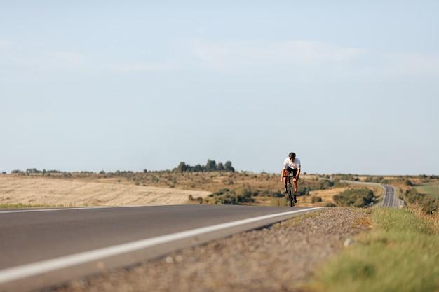 보호 헬멧 및 포장 도로에서 자전거를 타는 안경의 활성 스포츠맨, 낮은 각도보기