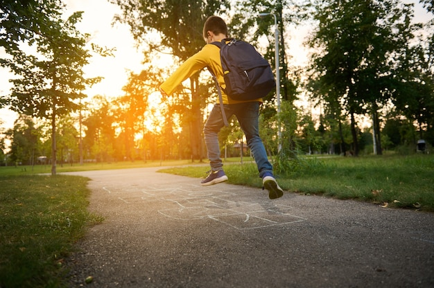 An active sporty boy with a school bag on his back plays hopscotch after school, takes turns jumping over the squares marked on the ground. street children's games in classics.