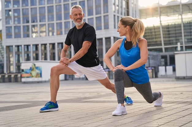 Active sporty middle aged couple man and woman stretching legs preparing for running together in