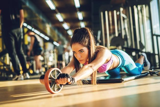 체육관에서 블랙 매트에 복근 롤러 휠로 운동을 하 고 활성 스포티 한 여자.