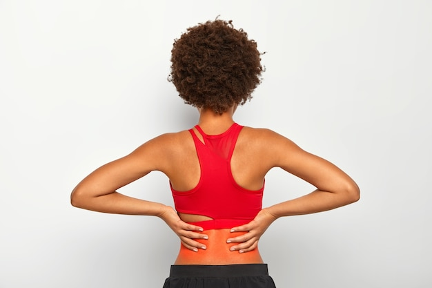 Active sporty woman has injured back after exercising or running, feels painful feeling in lower back, has curly hair, dressed in red top and trousers