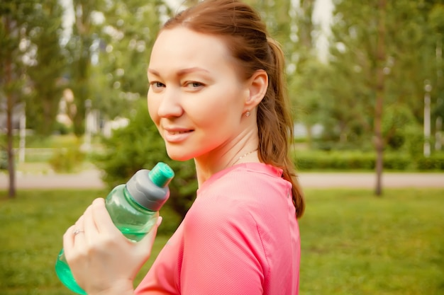 Active sporty woman holding bottle after training