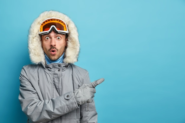 Active stupefied man trains in winter mountains goes snowboarding wears grey jacket and ski goggles indicates with surprised expression on empty space.
