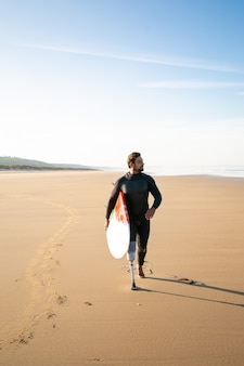 Active surfer with amputated leg walking on beach with surfboard. bearded amputee in wetsuit pacing on sand, carrying board and looking away