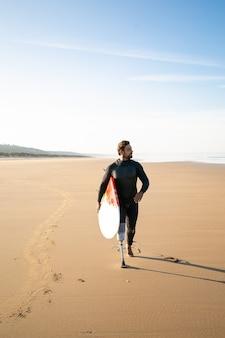 절단 된 다리가 서핑 보드와 함께 해변을 걷고있는 활성 서퍼. 잠수복을 입고 모래 위에 서서 보드를 들고 멀리 보는 수염 난 절단 환자