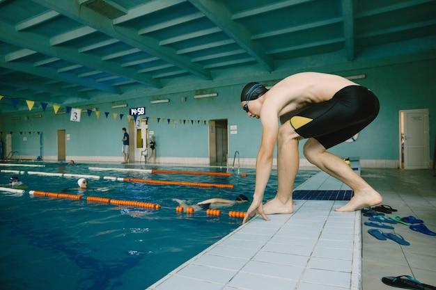 プールでジャンプするアクティブなスイマー、競技開始。屋内プール。ヨーロッパ人。