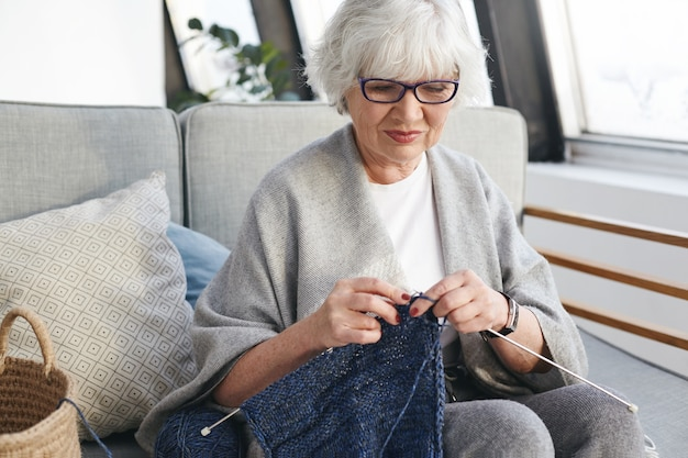 Active talented caucasian woman on retirement spending day indoors, knitting warm clothes for grandchildren, sitting on sofa in cozy interior, smiling. needlework, handicraft and hobby concept