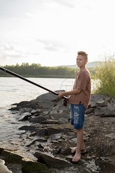 Активный мальчик-подросток с длинной удочкой стоит на берегу во время рыбалки