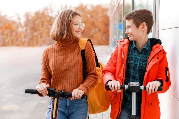 屋外でキックスクーターに乗っているアクティブなティーンエイジャー