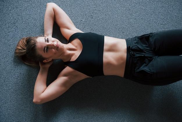アクティブなトレーニング。ジムの床で腹筋をしています。美しい女性フィットネス女性