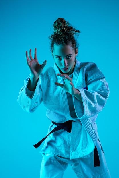 Active training. professional female judoist in white judo kimono practicing and training isolated on blue neoned studio background.