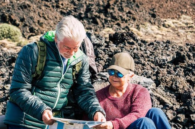 アクティブな旅行者の年配のカップルが一緒にトレッキングエクスカーションで地図をチェックします-山でアウトドアレジャー活動を楽しんでいる健康な成熟した引退した人々のライフスタイル-高齢者の観光コンセプト